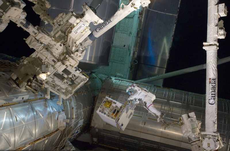 NASAs Real Gravity - Astronaut Mike Fossum Transfers the Robotics Refueling Mission Payload During A Spacewalk on July 12, 2011